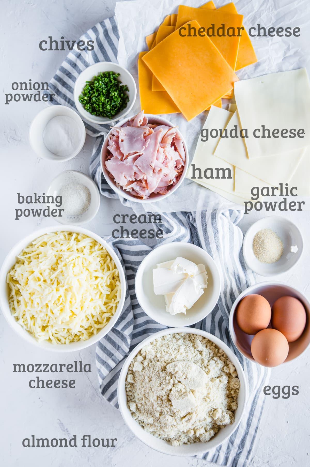 Ingredients laid out for keto hot pockets - cheddar, gouda, chives, ham, almond flour, eggs, cream cheese, mozzarella cheese, garlic powder, onion powder.
