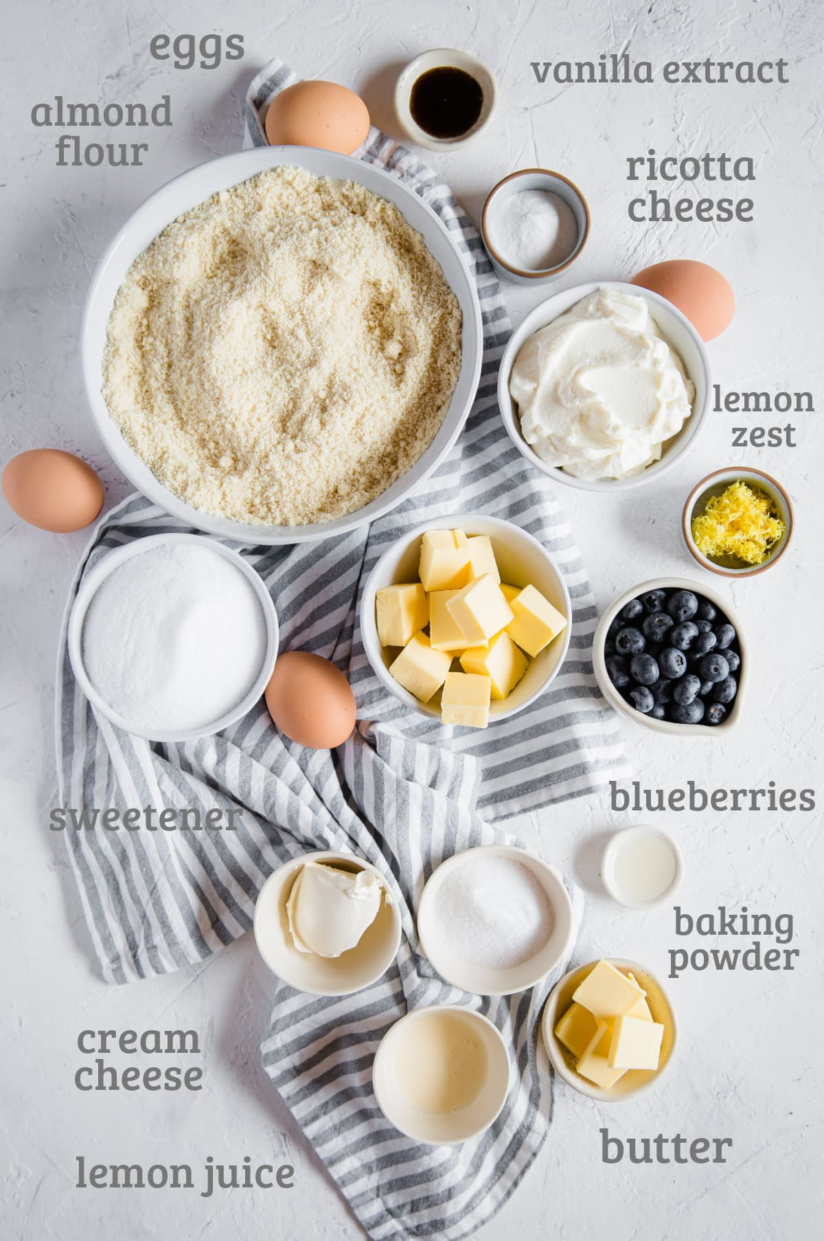 Ingredients for a low carb blueberry lemon pound cake - almond flour, sweetener, butter, vanilla, eggs, lemon, ricotta, blueberries