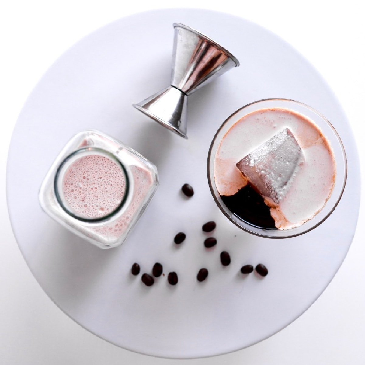 overhead shot of a glass of Keto Irish Cream on the rocks, a bottle of Irish cream, coffee beans, and a cocktail jigger