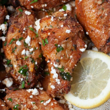 Metal serving dish with crispy chicken wings, topped with feta cheese and parsley, and garnished with lemon