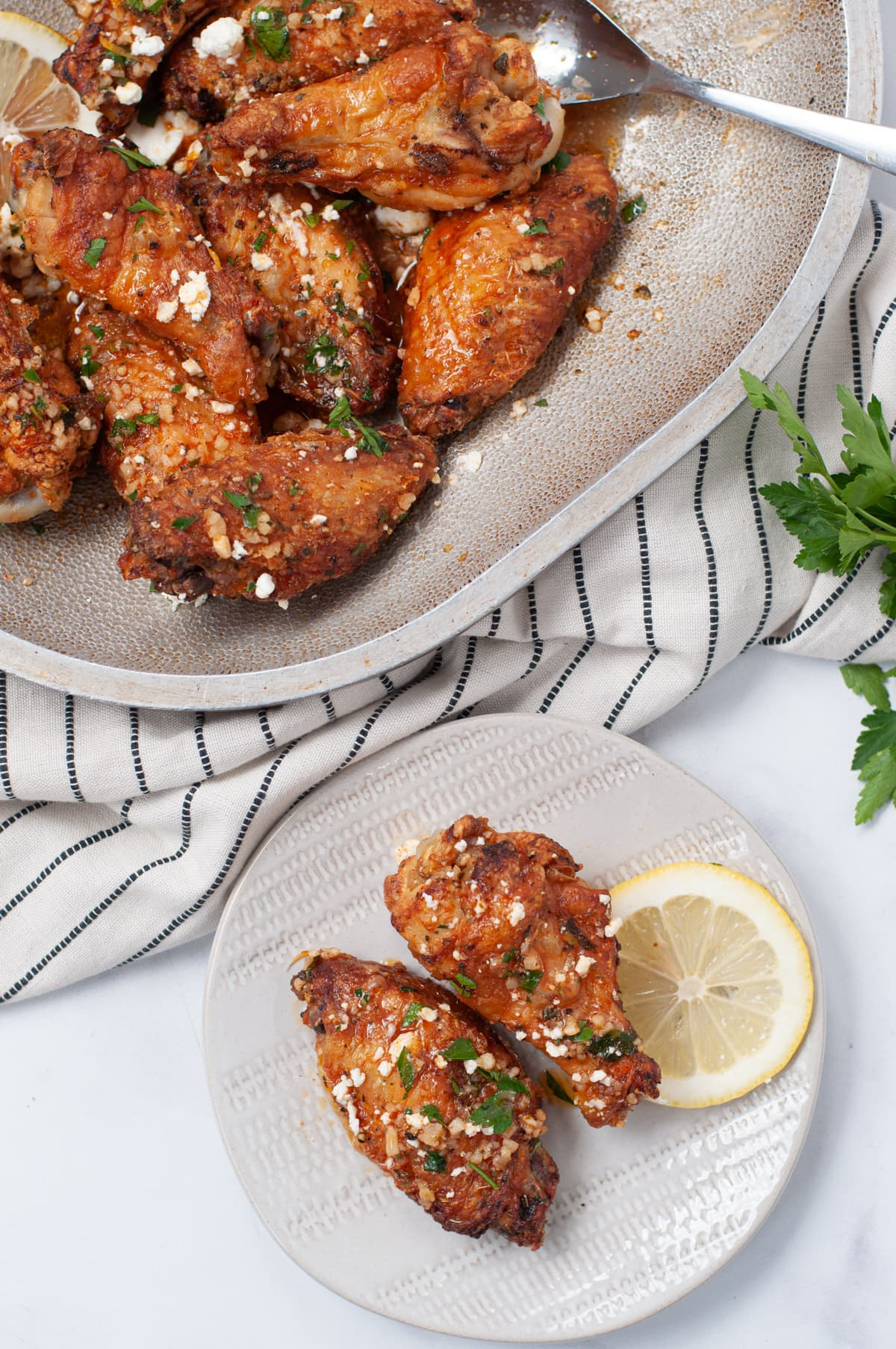 serving platter of chicken wings, next to a gray plate with 2 crispy chicken wings, topped with feta cheese and parsley