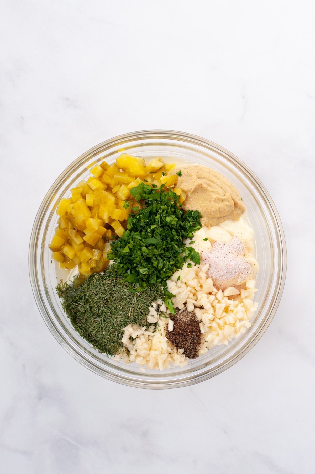 A mixing bowl with mayonnaise, dijon, pickles, garlic, dill, parsley, salt and pepper