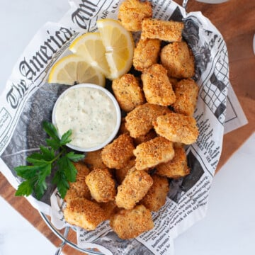 a wire basket lined with parchment paper, filled with keto fish sticks, tartar and lemon