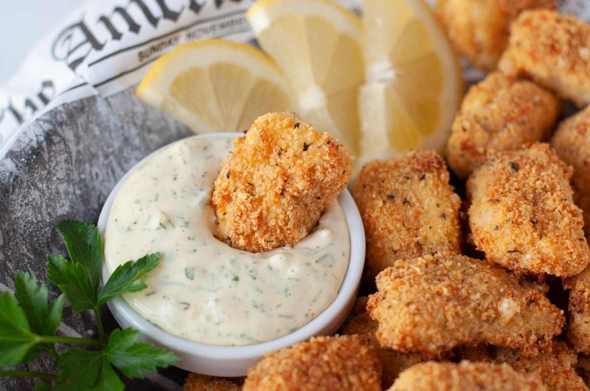 a basket of fish nuggets with one nugget in tartar, served with lemons
