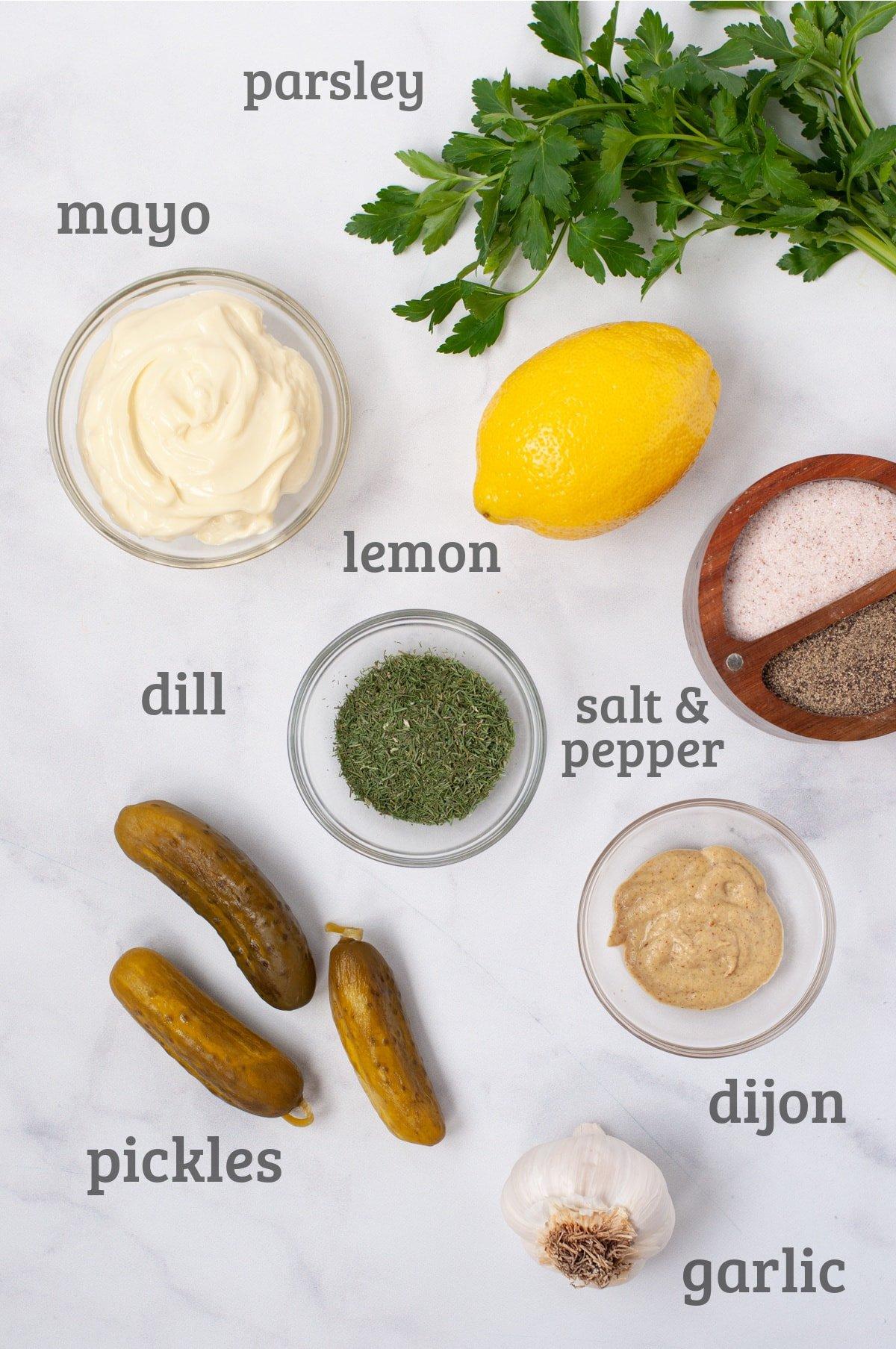 Ingredients for tartar sauce - parsley, lemon, mayo, dill, dijon, pickles, garlic, salt and pepper