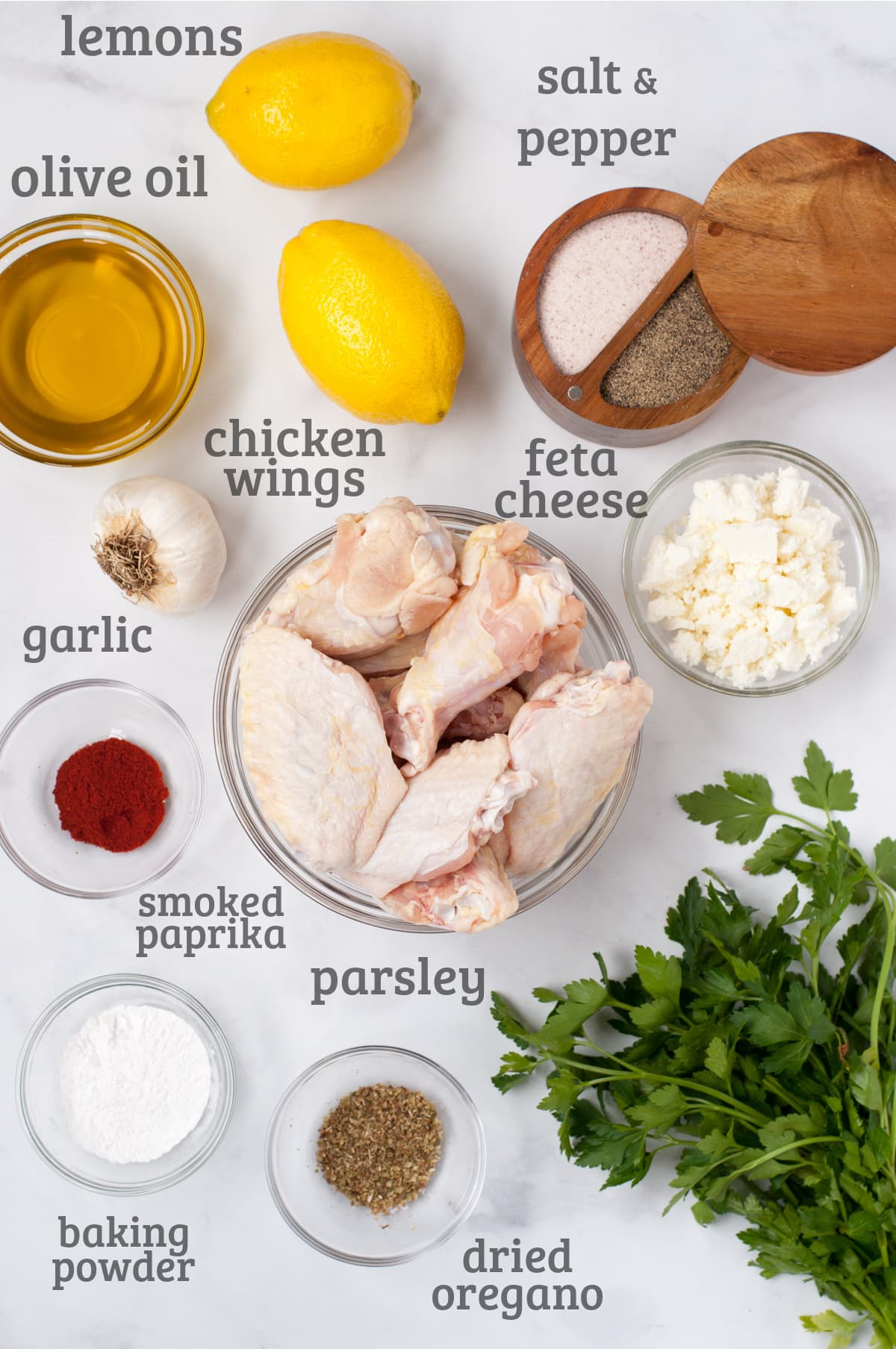 ingredients for lemon feta chicken wings - chicken, feta, lemons, garlic, olive oil, parsley, and spices