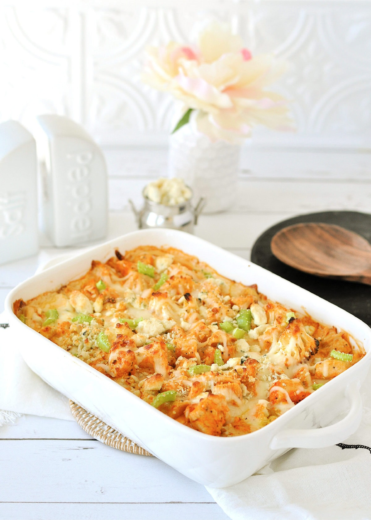 a white casserole dish, filled with buffalo chicken cauliflower Mac and cheese, with a white cloth and wooden serving spoon