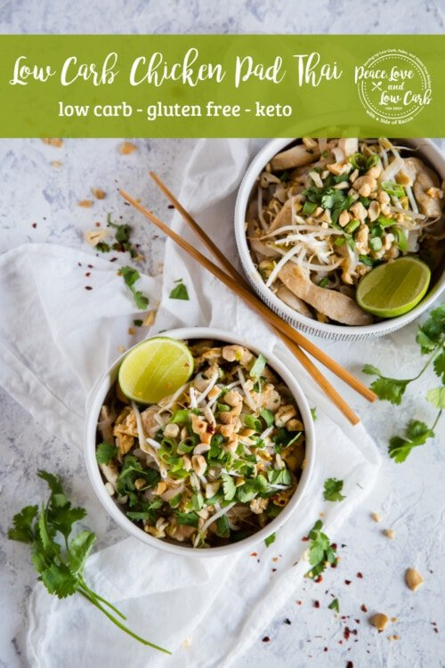 Two bowls of Keto Chicken Pad Thai garnished with red pepper flakes, cilantro, and lime in white bowls on a white background with wooden chopsticks and extra garnish sprinkled around.