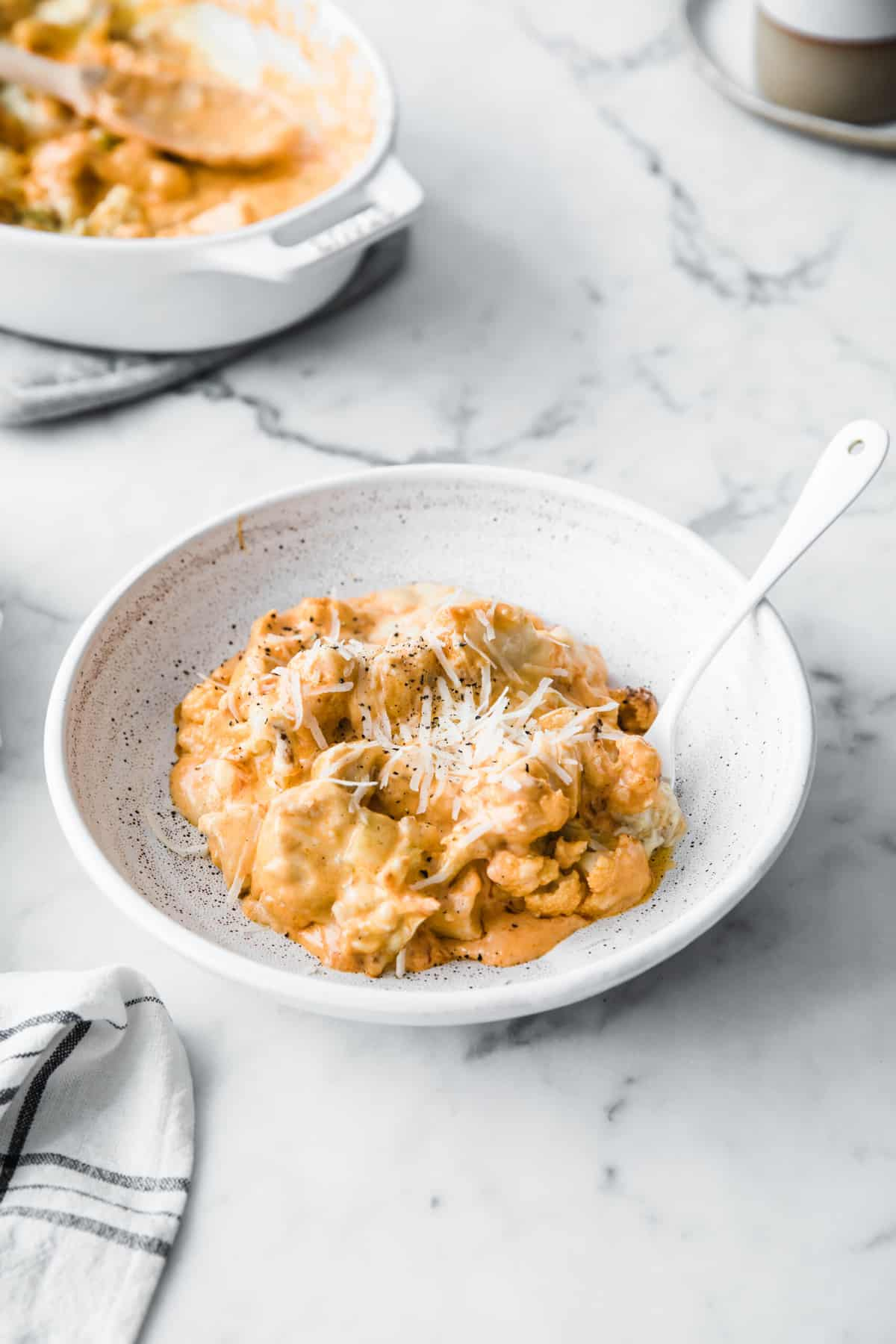 white casserole dish with low carb buffalo chicken Mac and cheese, with a wood serving spoon