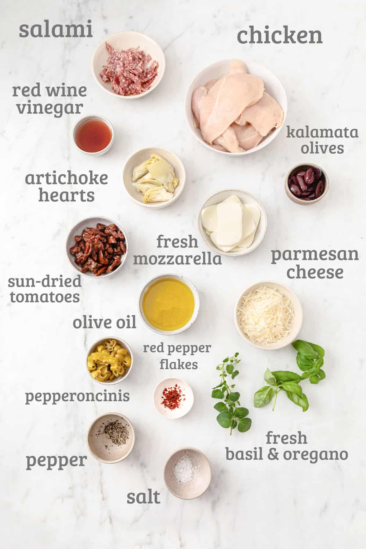 Ingredients for Antipasto Chicken - chicken, salami, artichokes, tomatoes, garlic, olives, basil, cheese, oregano, vinegar, garlic