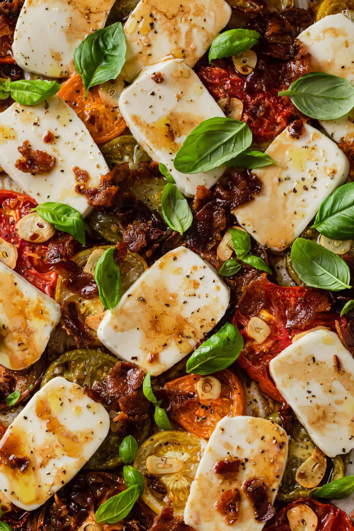 baking sheet with baked caprese salad - heirloom tomatoes, basil, fresh mozzarella, bacon, garlic, olive oil