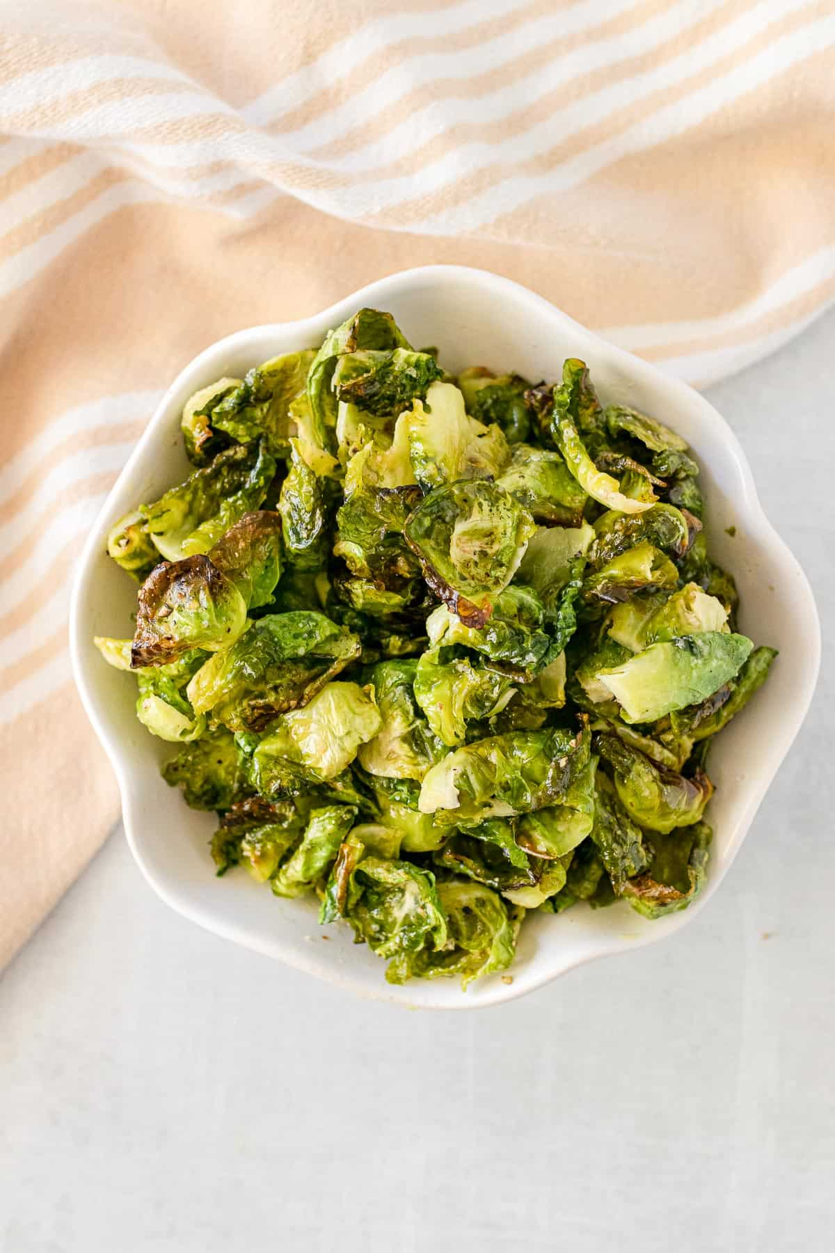 white bowl full of crispy Brussels sprouts chips, with fresh Brussels sprouts in the background