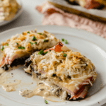 a rimmed baking sheet with parchment paper, topped with portobello mushrooms, cooked with Cordon Bleu toppings