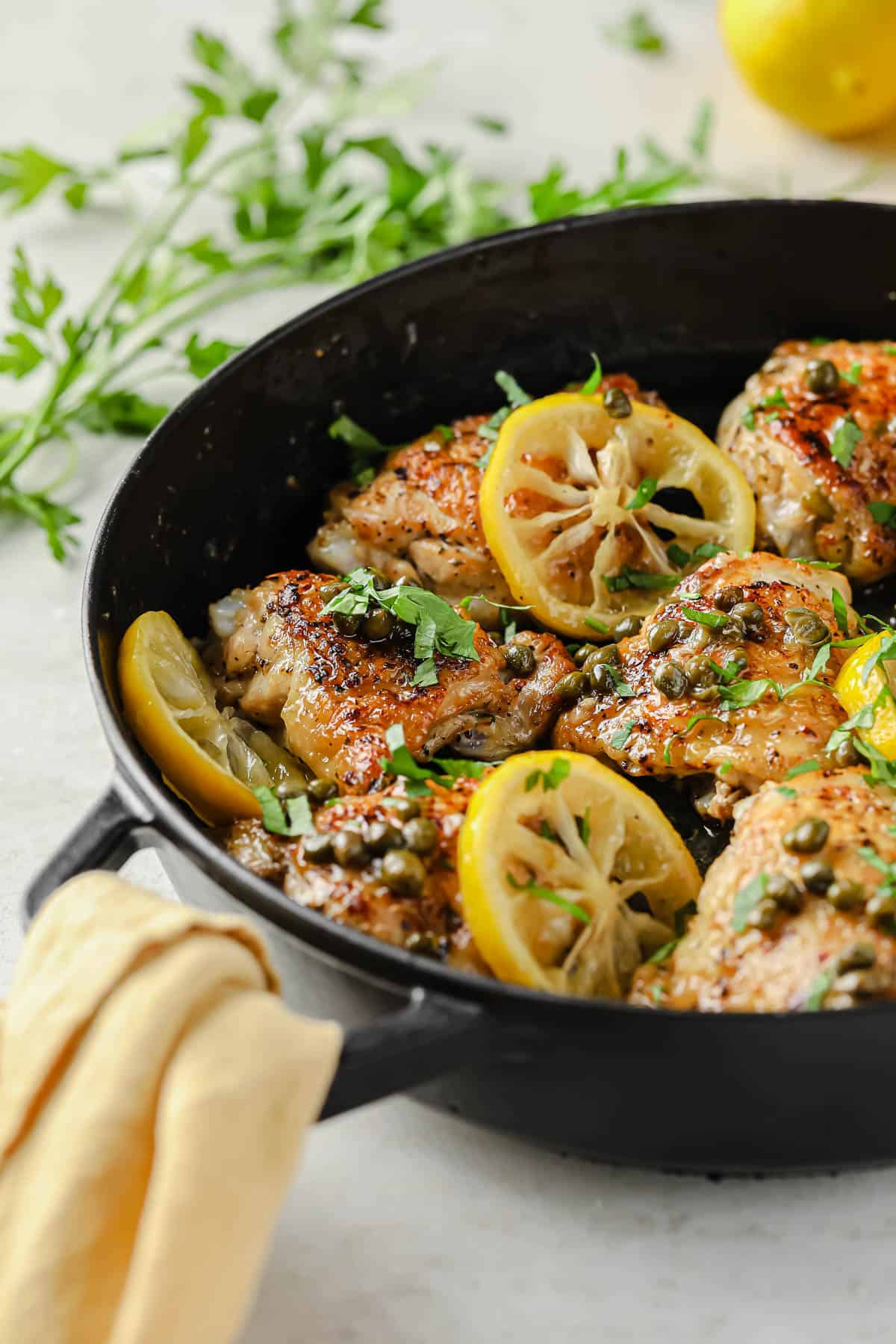 cast iron skillet full of crispy chicken thighs, lemon, capers, and fresh herbs