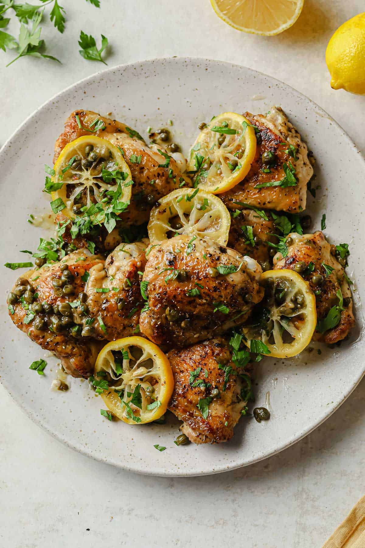 white plate full of keto chicken piccata - crispy chicken thighs, lemon, capers, and fresh herbs