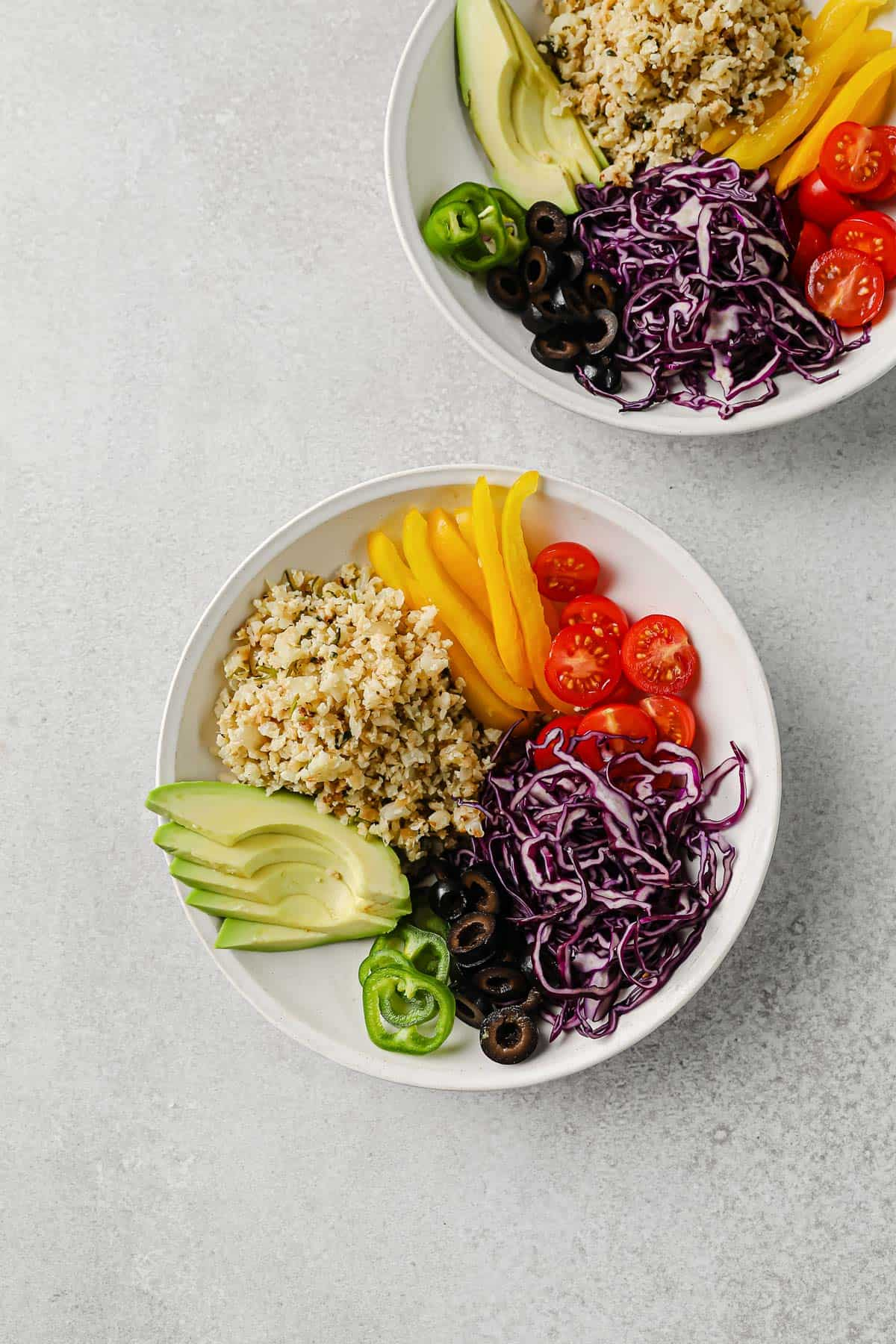 bowls piled with ingredients for fish taco bowls - cabbage, peppers, tomatoes, avocado, jalapenos, cauliflower rice