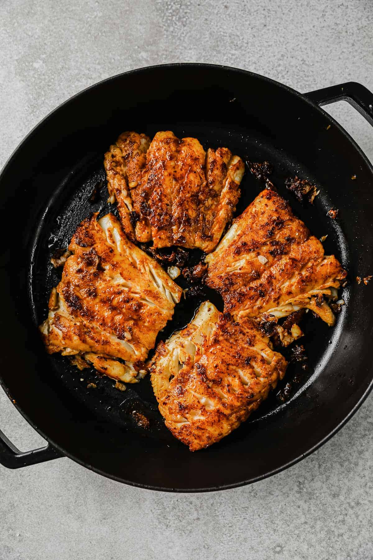 taco seasoned cod fillets being cooked in a cast iron pan