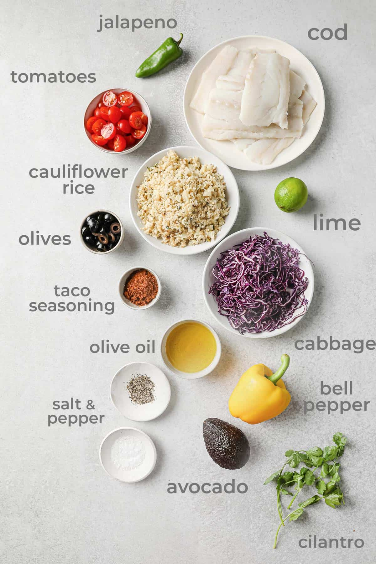 Ingredients for fish taco bowls - cod, cabbage, peppers, avocado, cilantro, limes, tomatoes taco seasoning
