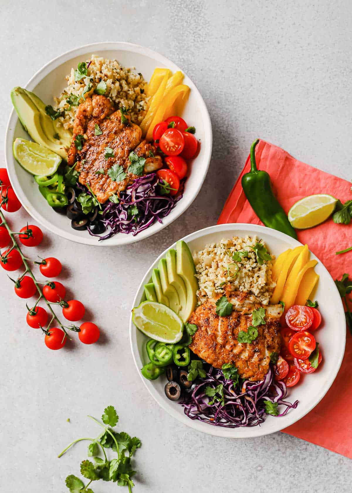 fish taco bowls with seasoned cod, olives, jalapenos, peppers, tomatoes, lime, cilantro, and cauliflower rice