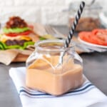 a jar of burger sauce with a burger, and bacon jam in the background