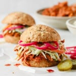 barbecue pulled pork sandwich with keto buns, barbecue pork, broccoli slaw, and pickled red onions