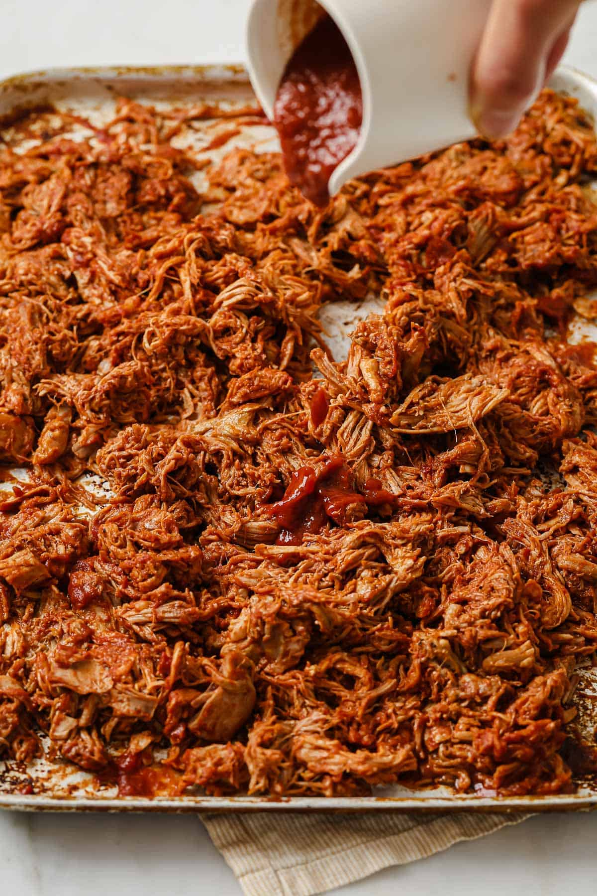 cooked and shredded pork butt, tossed with keto barbecue sauce, on a sheet pan
