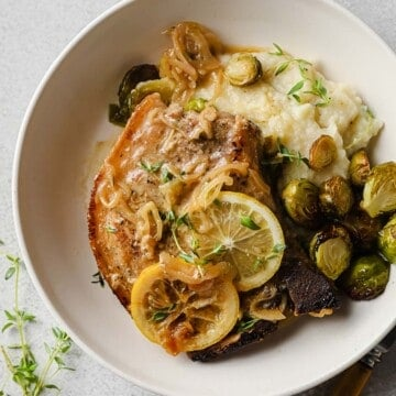 Lemon Thyme Pork Chops plated with mashed cauliflower and roasted brussels sprouts