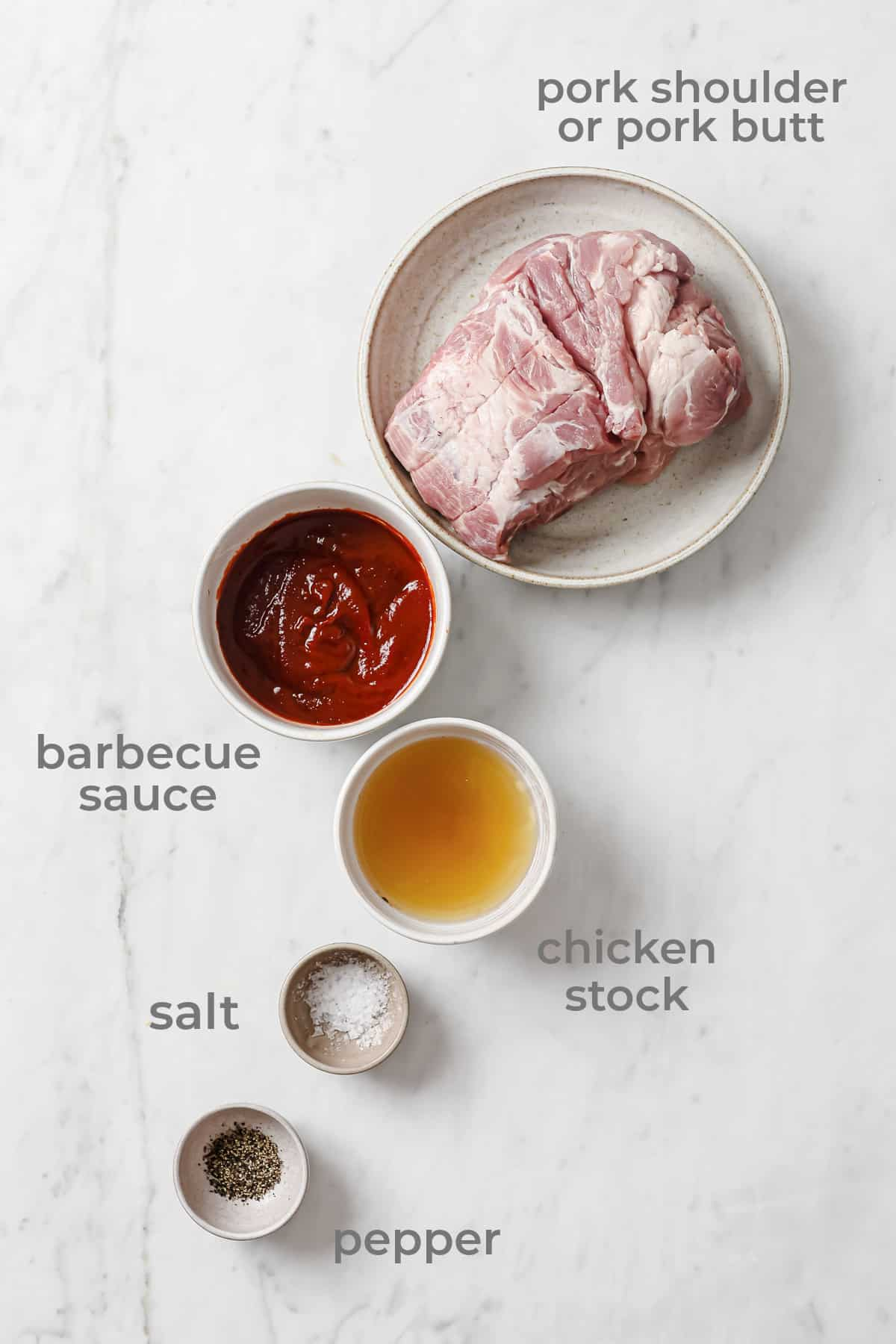 Ingredients to make keto barbecue pulled pork - pork shoulder, barbecue sauce, chicken stock, salt and pepper