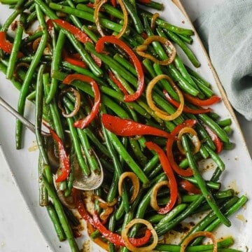 a white plate full of an asian inspired green bean dish - green beans, onion, peppers, soy sauce, butter, brown sugar