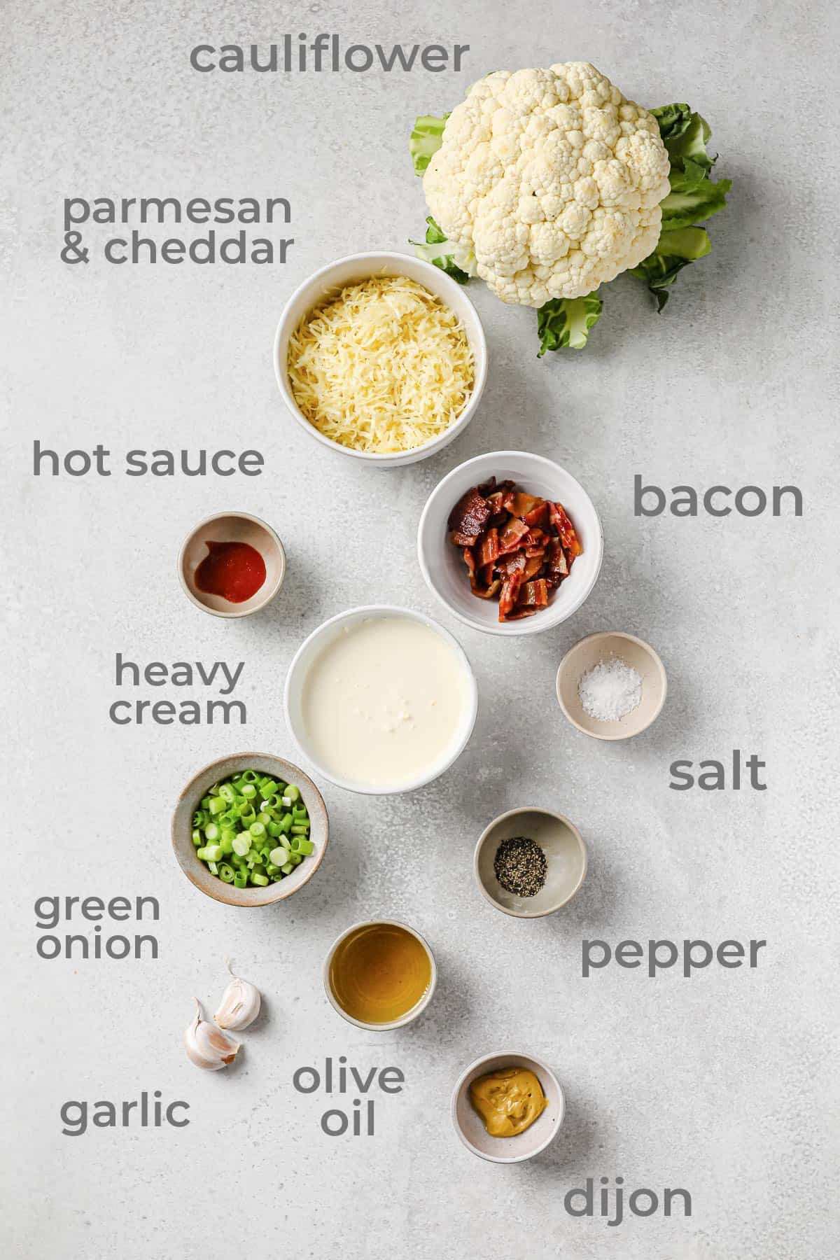 ingredients laid out - bacon, cheese, garlic, mustard, cauilflower, green onions, bacon, cheese, salt, and pepper