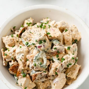 white bowl full of low carb chicken salad with bacon, jalapeños, onion, and green onions