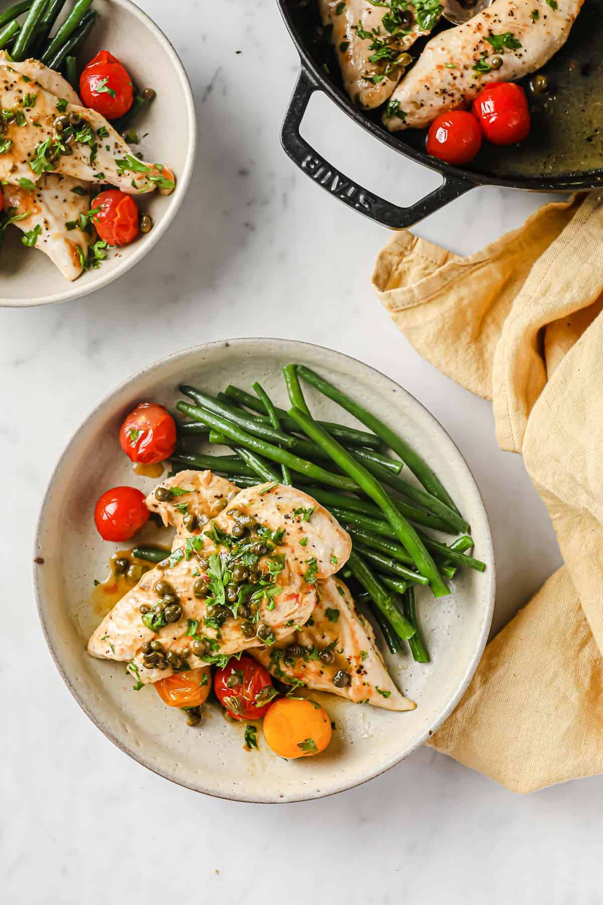 sautéed chicken cutlets with lemon butter caper sauce, served with blistered tomatoes and green beans