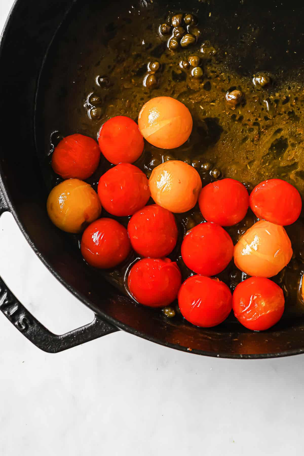 cast iron skillet with lemon butter sauce, capers, and tomatoes