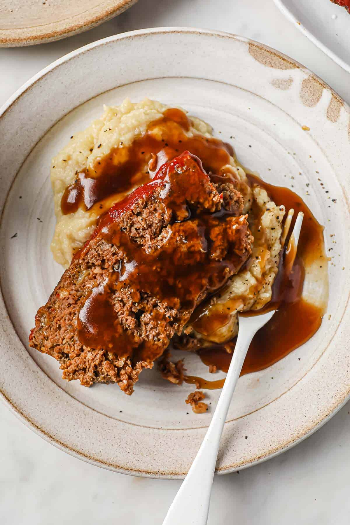 meatloaf with cauliflower mash and gravy, served on a white plate