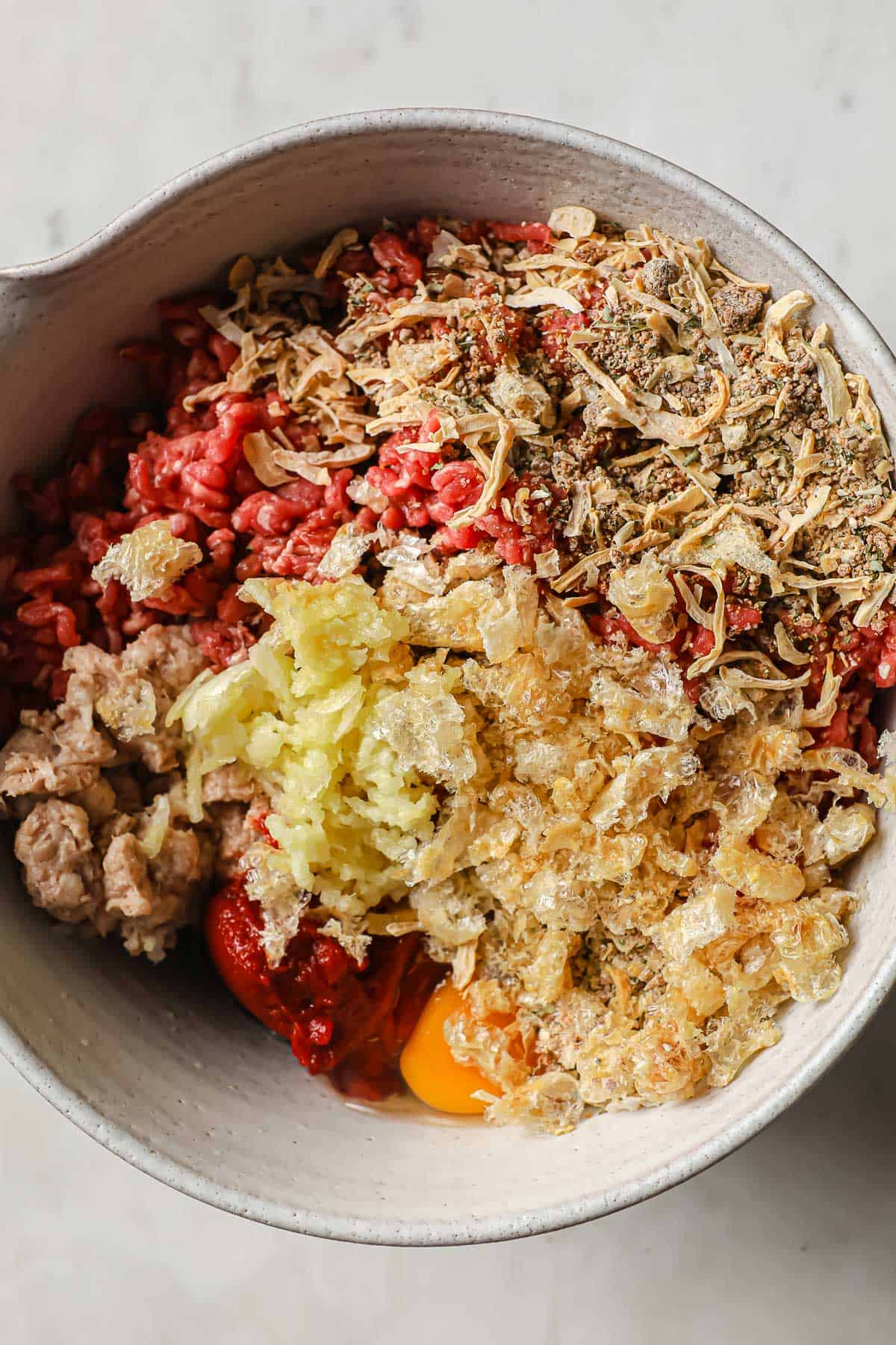ingredients for meatloaf - beef, sausage, tomato paste, eggs, onion soup, garlic in a mixing bowl