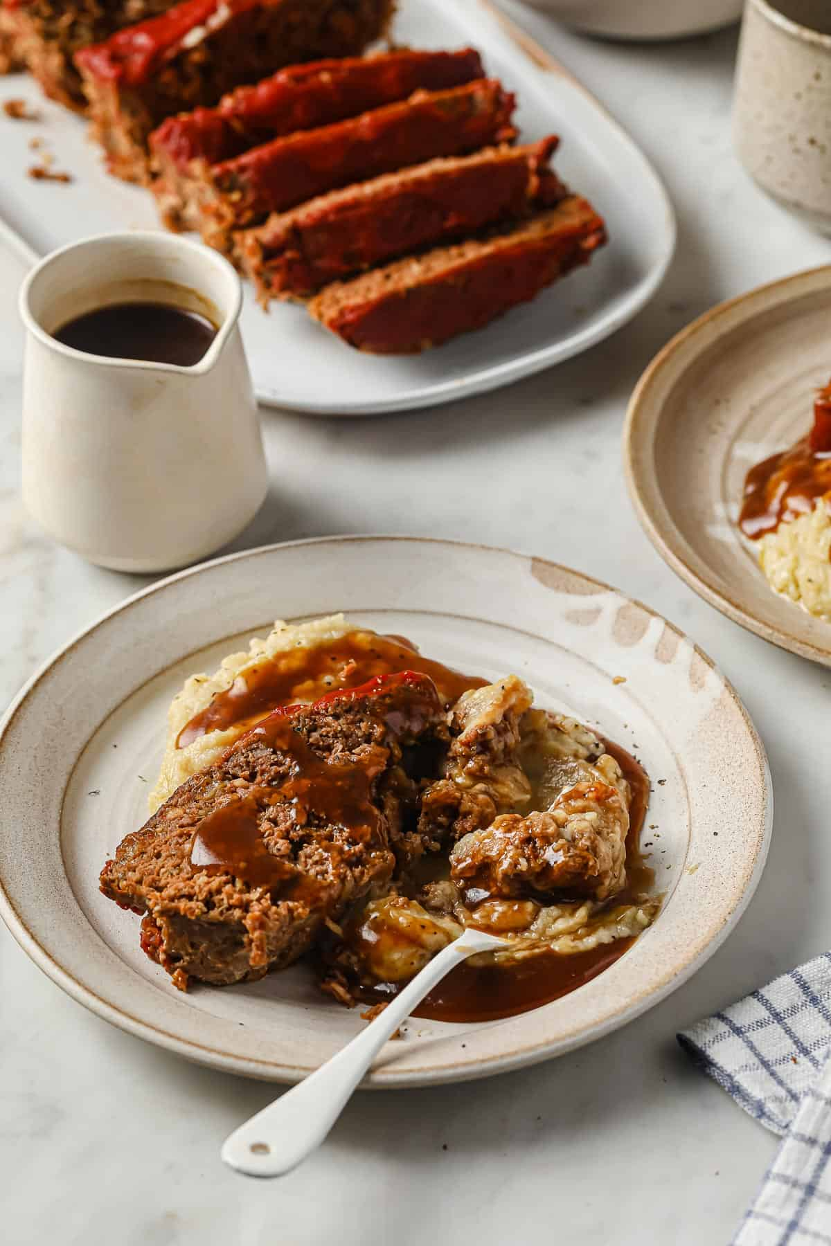 Meatloaf with cauliflower mash and gravy served on a white plate