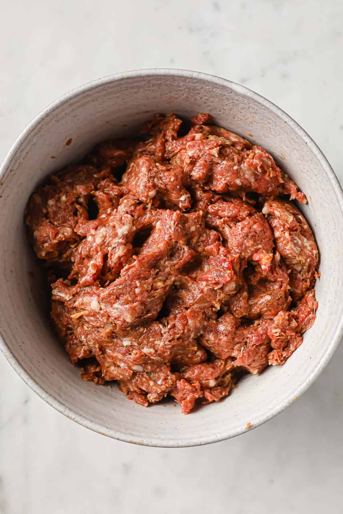ingredients for meatloaf - beef, sausage, tomato paste, eggs, onion soup, garlic all mixed up