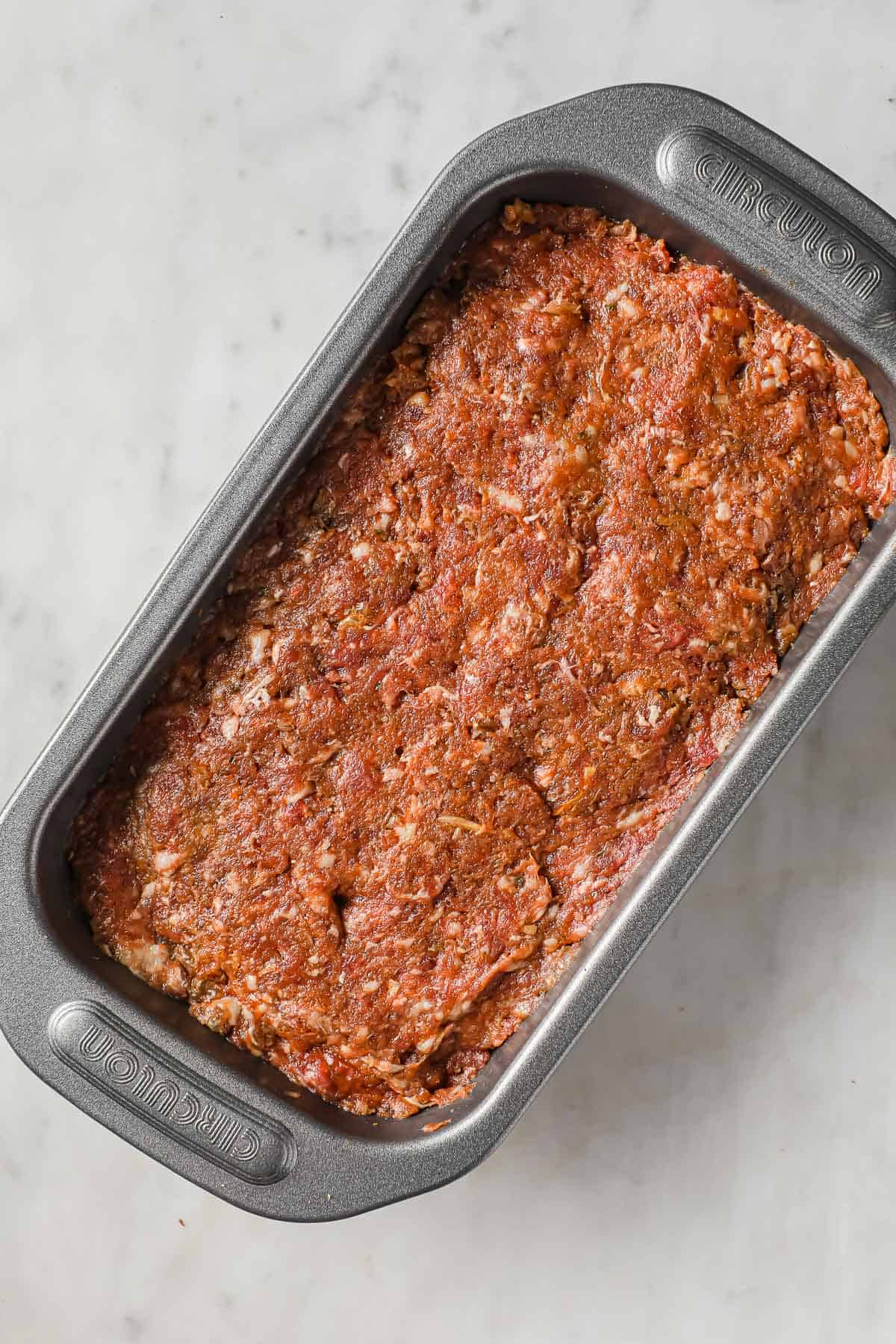 ingredients for meatloaf - beef, sausage, tomato paste, eggs, onion soup, garlic all mixed up and in a loaf pan