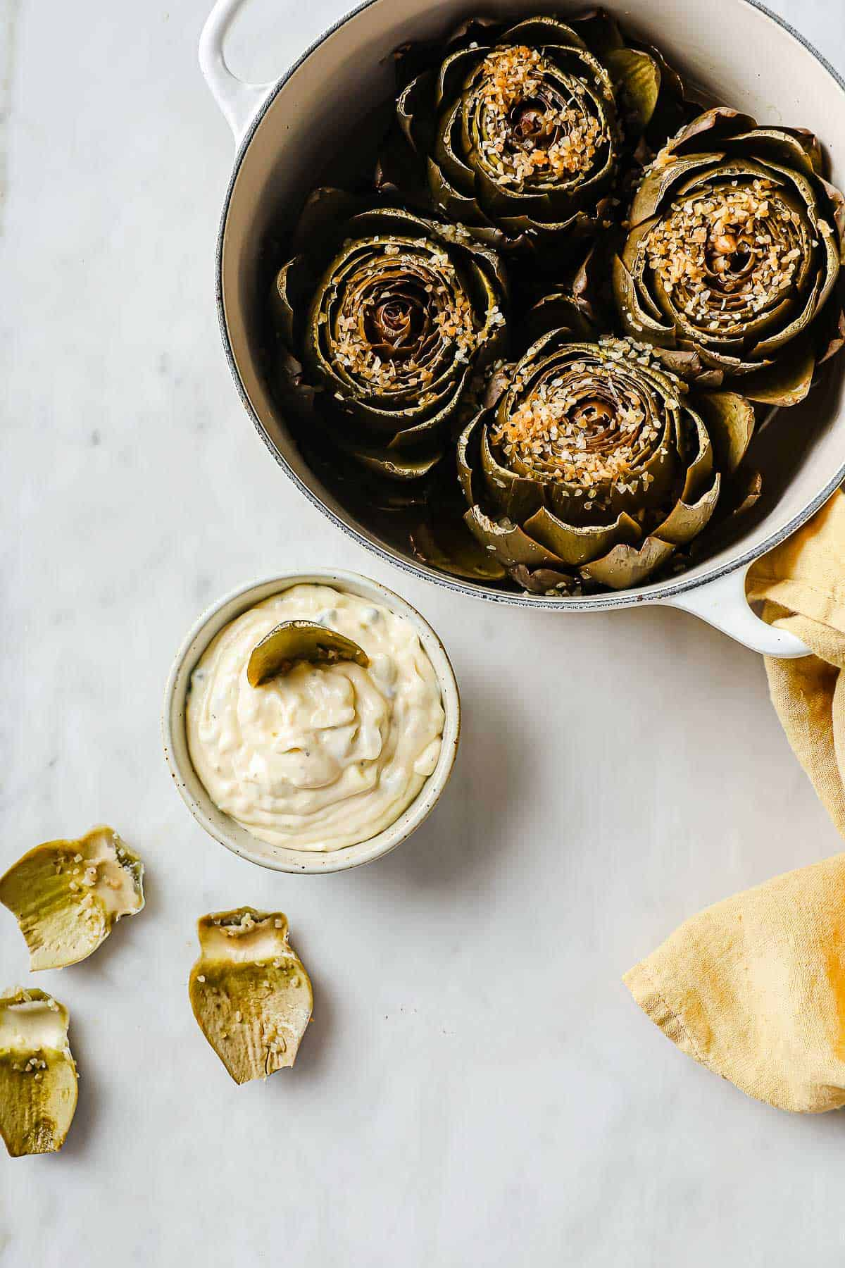 steamed artichokes with plucked leaves next to them, served with a lemon caper aioli sauce